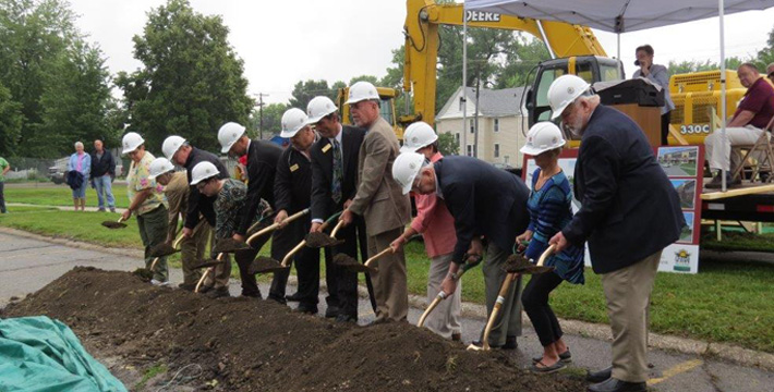 Groundbreaking participants, left to right: 1.     Char Thompson, 21-year Mayflower CMA, representing Mayflower staff, 2.     Lorna Caulkins, future Watertower Square resident, 3.     Jo Wray, City of Grinnell Council Member, 4.     Rick Ramsey, Ramsey-Weeks, Inc., Watertower Square sales agency, Chair of the Board, 5.     Adam Papesh, Story Construction, Ames, general contractor, project manager, 6.     Jack Morrison, Mayflower Community Director of Facilities Services, Watertower Square owner's representative, 7.     Austin Jones, Grinnell State Bank Executive Vice-President, project lender, 8.     Don Schild, Mayflower Community Board of Trustees President, 9.     JoAnn Britton, Mayflower Foundation Boards Secretary/Treasurer, 10. Bob Mann, Mayflower Community Executive Director, 11. Jeananne Schild, Mayflower Residents Association President-Elect, 12. Gordon Canfield, City of Grinnell Mayor.   At the podium is Mayflower's chaplain, Rev. Christin Tinker, performing the blessing of the ground.  Seated on the platform are speakers, Shane Estes, Mayflower Residents Association President, and Dan Agnew, future Watertower Square resident.