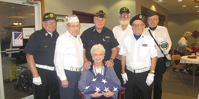 Seated--St. Francis Manor resident Evelyn Felper holding the flag in honor of her late husband and veteran, Gordon Felper. Standing L-R: Larry Ellis, Ed Adkins, Dick Gustafson, Leroy Runner, George Fowler and Richard Brignon representing the Grinnell Ceremonial Unit.
