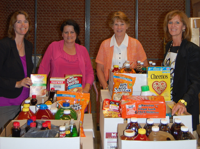 Members of Grinnell Mutual's Employee Events Committee (from left) Lori Smith, Diane Hall, Gale Larson, and Barb Baker organize food donations from one of many company food drives for the MICA Food Pantry.