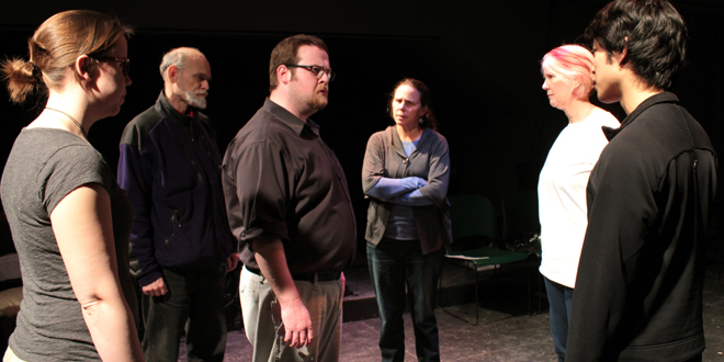 Biedermann, portrayed by Luke Saunders, (center) is confronted by members of the Chorus (from L to R: Kate Baumgartner, William Crosby, Wendy Abrahamson, Catherine Rod, and Alex Hsieh) in Grinnell Community Theatre's production of The Arsonists to be staged February 19 – 22 in the Loft Theatre at the Grinnell Arts Center.
