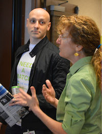 """Sam Coster sports an event t-shirt (printed by Ballyhoo Ink of Grinnell) while listening to Colleen Reardon, the Blood & Marrow Transplant Program Manager at the University of Iowa, explain the difference between donation procedures to new registry members."""