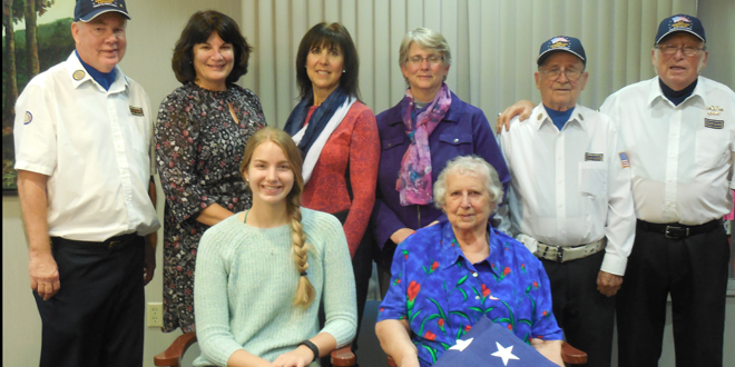 Seated—Seeland Park resident Agnes Mikel holding the flag in honor of her late husband and veteran, Mike Mikel with her granddaughter, Mariah Mikel Standing L-R: Ron Davis, Brenda Mikel Hagedorn, Debra Mikel Styers, Connie Mikel Weir, George Fowler, and Larry Ellis
