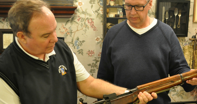 Dave Smith (L) and his brother Bill show collected war antiques that are displayed at Smith Funeral Home