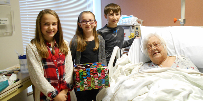 Helga Rhinehart, Brooklyn, enjoyed a little holiday cheer from three HLV sixth graders. From left, standing were Emma Schafbuch, Chelle Thys, and Ben Thys, with Rhinehart.