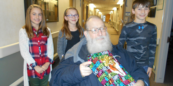 John Spake, Marengo, received a present from HLV sixth graders. Making the trip to GRMC on Christmas day to pay it forward were, from left, Emma Schafbuch, Chelle Thys, and Ben Thys, with Spake in the chair.
