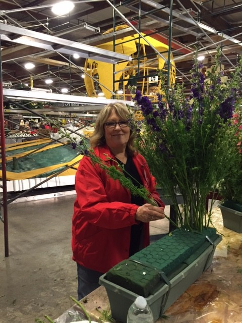 Local florist Cynthia Sherman works on the award-winning Kiehl's float. (photo courtesy of Cynthia Sherman)