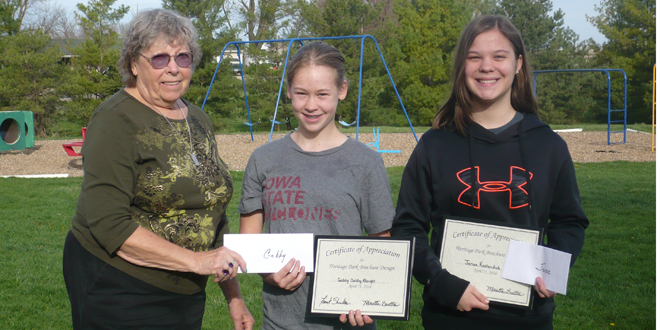 l-r, Maretta Gratton, member of the Heritage Park Board, presents certificates and prizes for outstanding Park brochure creations by first place prize winner, Gabby Dahlby Albright, and second prize winner, Jenae Kastendick, students at Central Iowa Christian School.