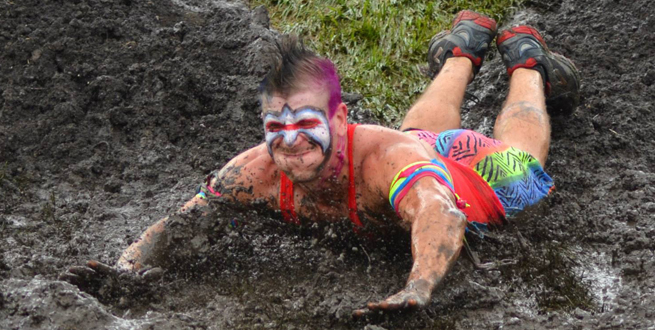 Warrior Run: Jacob Chandler from Grinnell goes down the mud slide head first at the Warrior Run, a mud and obstacle run at Grinnell Games.