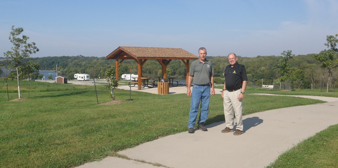 Frank Brownell and Mark Vavroch, County Conservation Director, walk along Stagecoach Trail at Diamond Lake. Mr. Brownell has helped fund many projects at Diamond Lake, including the trail, shelter, and new campground shown in the background.  Recently, he has continued his support to County Conservation by providing a large gift to the Poweshiek County Conservation Endowment Fund.