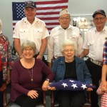 Seated—Seeland Park resident Jane Thompson holding the flag in honor of her late husband and veteran, Don Thompson with her daughter, Claudia Brammer from Rosemount, Minnesota. Standing L-R: Dorothy Peak, Don Thompson's sister; Larry Ellis, Ron Davis, Ed Adkins, George Fowler, and Jane's granddaughter, Danae (Carroll) Hewitt with her daughters, Sadie and Ruthie from Ankeny.